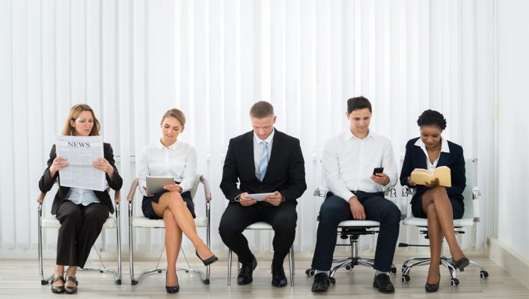 candidates sit in a waiting room for a job interview