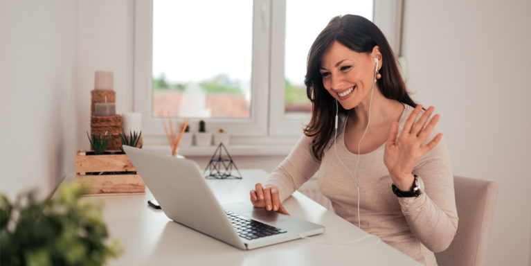 woman waving at her colleagues on a laptop meeting