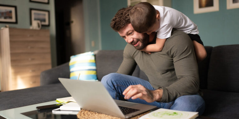 son climbing on father's back while father is working from home