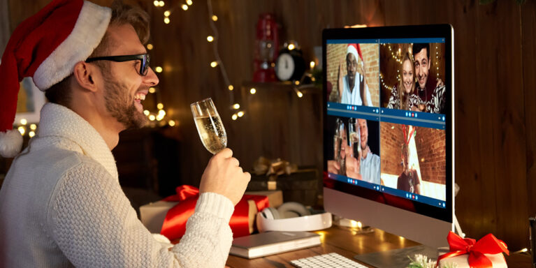 Man wearing Santa hat holding a champagne glass while attending a virtual holiday celebration with others on his computer screen