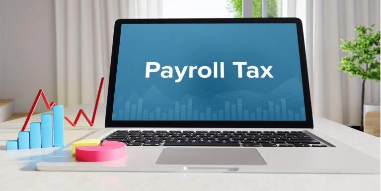 "Open laptop on a desk with the words ""Payroll Tax"" written on the screen, while a 3-D pie graph, line chart, and bar chart are showing payroll data."