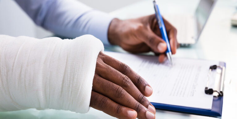 Zoomed in image of a man filling out a medical claim form, with one arm in a cast