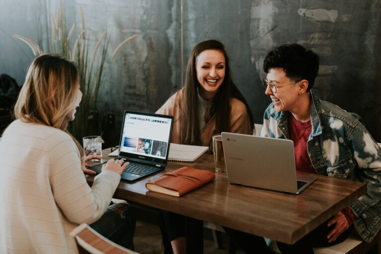 image of three diverse young employees sitting around a table working and laughing
